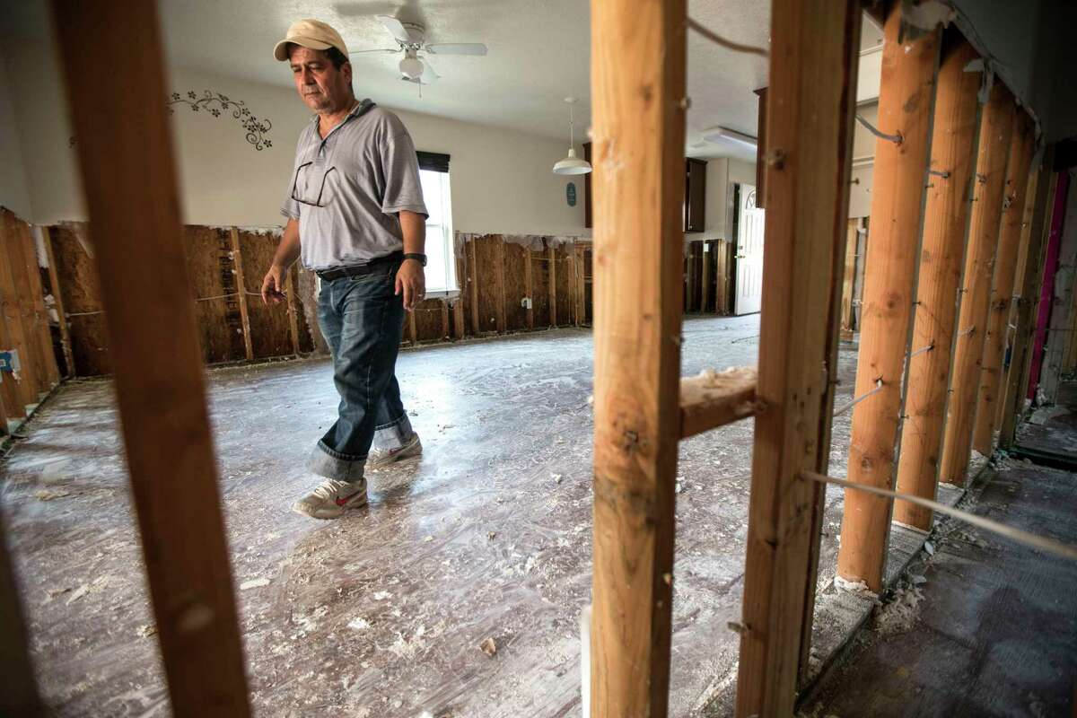 Driss Lassile walks through his house - heavily damaged by floodwaters from Tropical Storm Harvey - after volunteers from Habitat for Humanity helped clean out his flood-damaged home on Saturday in Independence Heights.