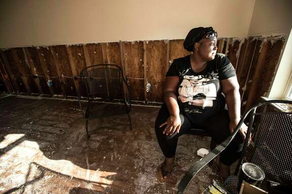 Neketta Shafer sits in her living room after volunteers from Habitat for Humanity helped removed sheetrock from her flood-damaged home on Saturday.