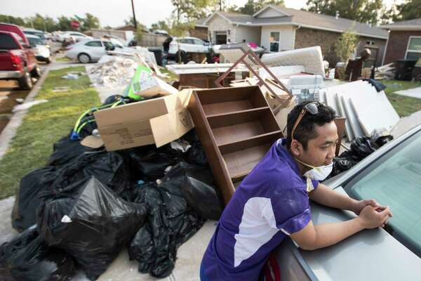 Vial Sum takes a break outside his brother's home damaged by floodwaters from Tropical Storm Harvey in a neighborhood built by Habitat for Humanity on Saturday.