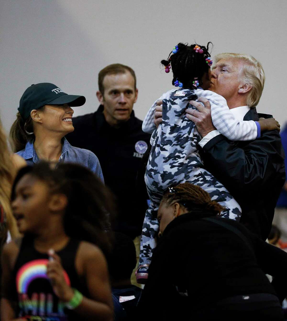 President Donald Trump kisses a child while visiting Tropical Storm Harvey evacuees at NRG Center with his wife, Melania.