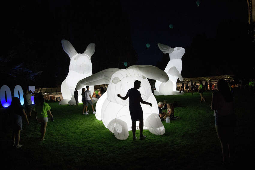 Festivalgoers hangout around giant inflatable rabbits during the second day of Bumbershoot at Seattle Center on Saturday, Sept. 2, 2017.
