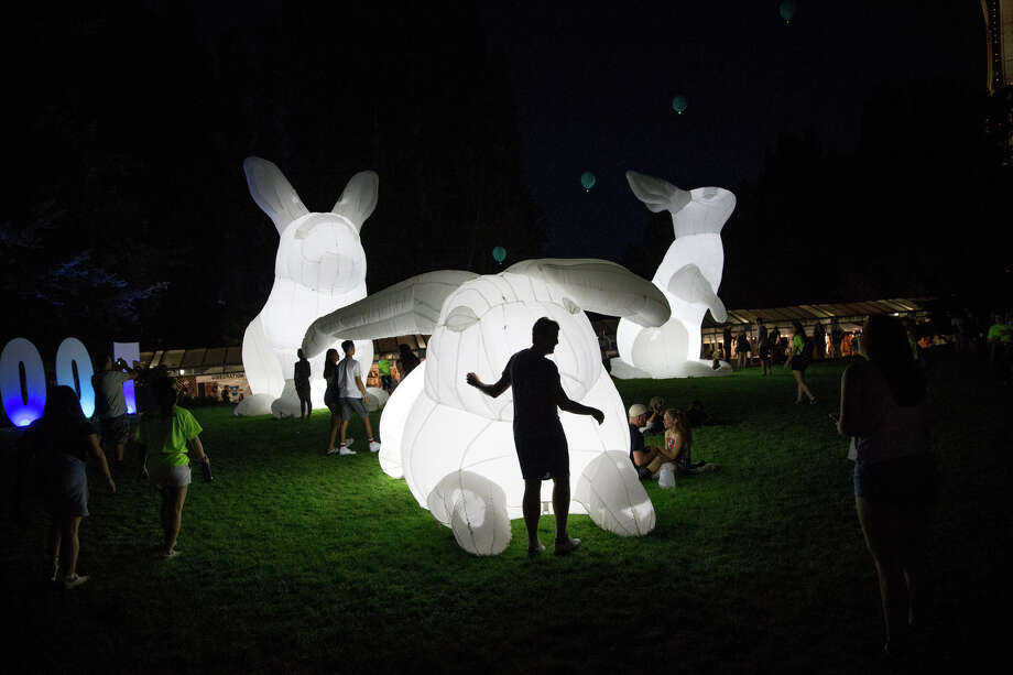 Festivalgoers hangout around giant inflatable rabbits during the second day of Bumbershoot at Seattle Center on Saturday, Sept. 2, 2017. Photo: GRANT HINDSLEY, SEATTLEPI.COM / SEATTLEPI.COM