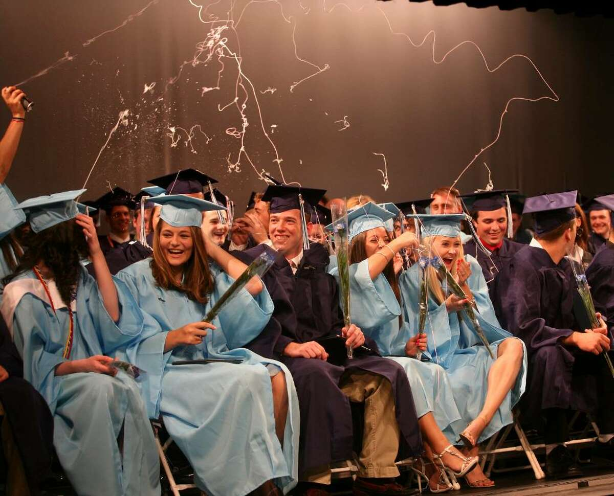 Graduates are showered in silly string by their classmates at the conclusion of Oxford High School's inaugural graduation on Monday, June 21, 2010.