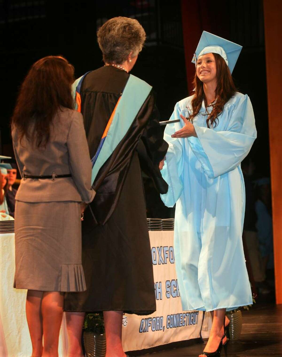 Meliisa Babina, right, receives the very first diploma ever from Oxford High School and Superintendent Judith Palmer at the school's inaugural graduation on Monday, June 21, 2010.