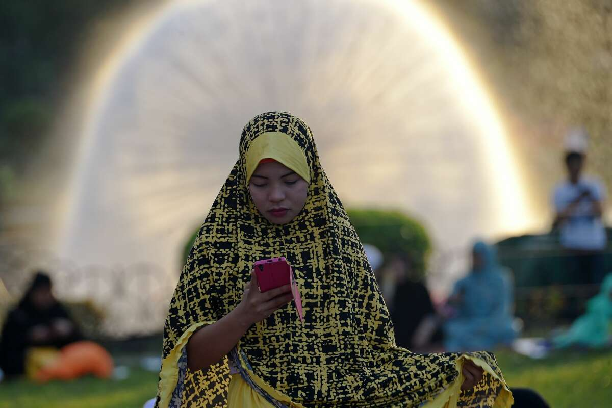 """A Filipina Muslim woman uses her mobile phone prior to attending prayers for Eid al-Adha at a park in Manila on September 1, 2017. Muslims around the world are celebrating Eid al-Adha, the """"Feast of Sacrifice"""", which marks the end of the annual pilgrimage or hajj to the Saudi holy city of Mecca and in remembrance of Abraham's readiness to sacrifice his son to God."""