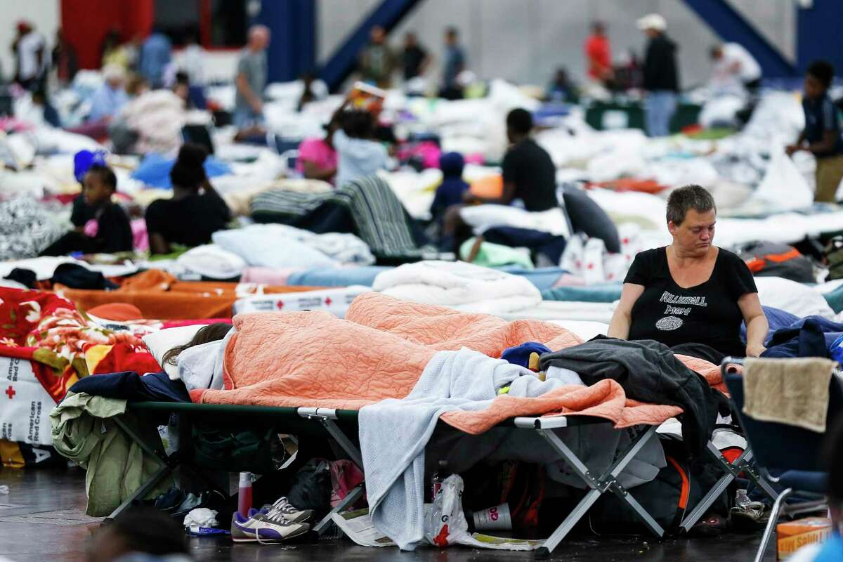 Mary Colson sits on a cot at the George R. Brown Convention Center where nearly 10,000 people took shelter after Tropical Storm Harvey on Aug. 30.