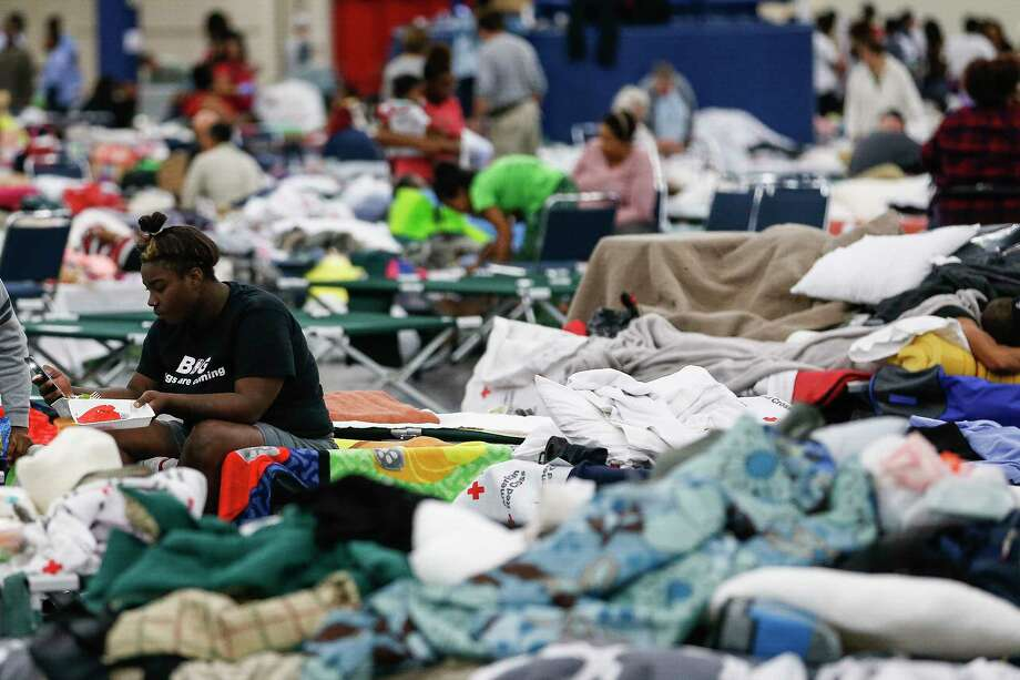 Markia Evans sits on a cot at the George R. Brown Convention Center where nearly 10,000 people are taking shelter after Tropical Storm Harvey Wednesday, Aug. 30, 2017 in Houston. ( Michael Ciaglo / Houston Chronicle) Photo: Michael Ciaglo, Staff / Michael Ciaglo