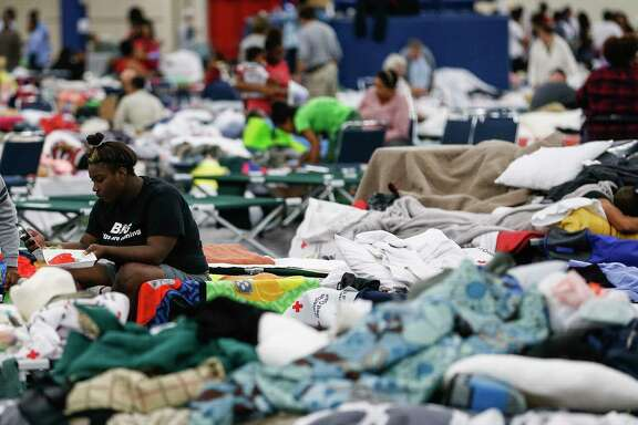 Markia Evans sits on a cot at the George R. Brown Convention Center where nearly 10,000 people are taking shelter after Tropical Storm Harvey Wednesday, Aug. 30, 2017 in Houston. ( Michael Ciaglo / Houston Chronicle)