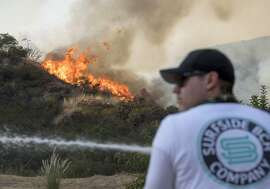 Aaron Funk watches the fire come down the side of the hill behind the home of his parents in Sun Valley neighborhood, north of Los Angeles on Saturday, Sept. 2, 2017. The wildfire just north of downtown had grown to the largest in city history, Mayor Eric Garcetti said. (Paul Rodriguez/The Orange County Register via AP)