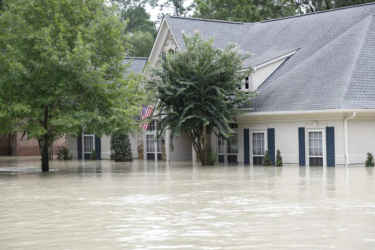 A Kingwood home is covered in 6 to 7 feet of water, flooded by the San Jacinto River in the wake of Harvey. A Kingwood woman fell in her flooded home and ended up dying from flesh-eating bacteria acquired through the injury. Her death was added on Sept. 25 to Harris County's official list of storm fatalities.