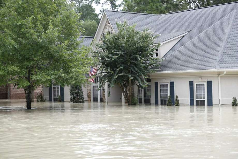 A Kingwood home is covered in 6 to 7 feet of water, flooded by the San Jacinto River in the wake of Harvey. A Kingwood woman fell in her flooded home and ended up dying from flesh-eating bacteria acquired through the injury. Her death was added on Sept. 25 to Harris County's official list of storm fatalities. Photo: Karen Warren /Houston Chronicle / @ 2017 Houston Chronicle