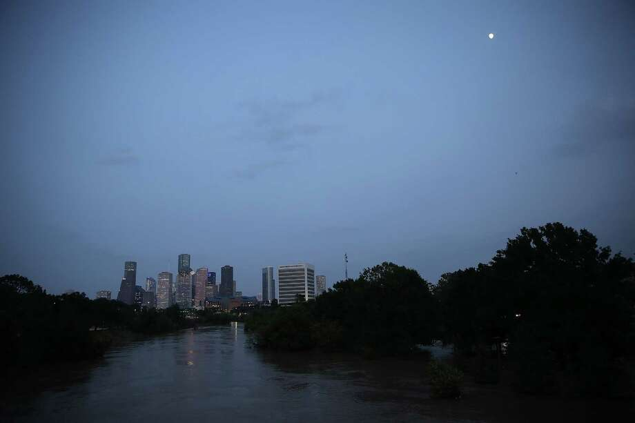 Buffalo Bayou, swollen with floodwaters in the wake of Hurricane Harvey, is shown with the Houston skyline in the background Friday. Buffalo Bayou is expected to remain at flood levels for at least 10-15 more days, resulting in many neighborhoods north and west of downtown being submerged until floodwaters recede.  (Photo by Win McNamee/Getty Images) Photo: Win McNamee, Staff / 2017 Getty Images
