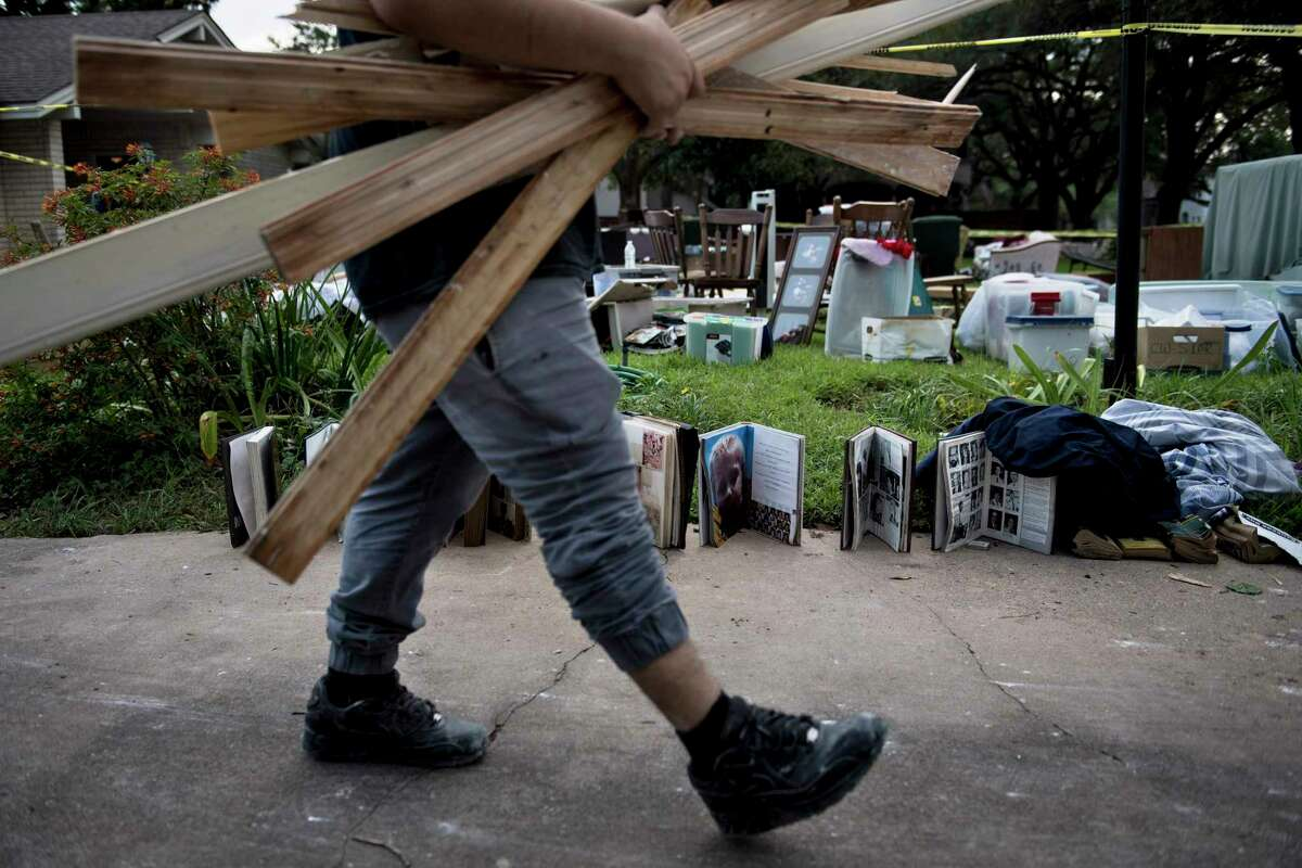 A worker carries water damaged wood as he passes salvaged personal items from a once flooded home as residents begin the recovery process from Hurricane Harvey. (Brendan Smialowski / AFP/Getty Images)