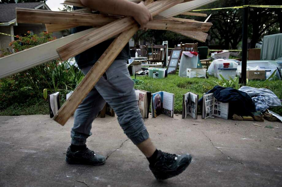 A worker carries water damaged wood as he passes salvaged personal items from a once flooded home as residents begin the recovery process from Hurricane Harvey. (Brendan Smialowski / AFP/Getty Images) Photo: BRENDAN SMIALOWSKI, Contributor / AFP or licensors