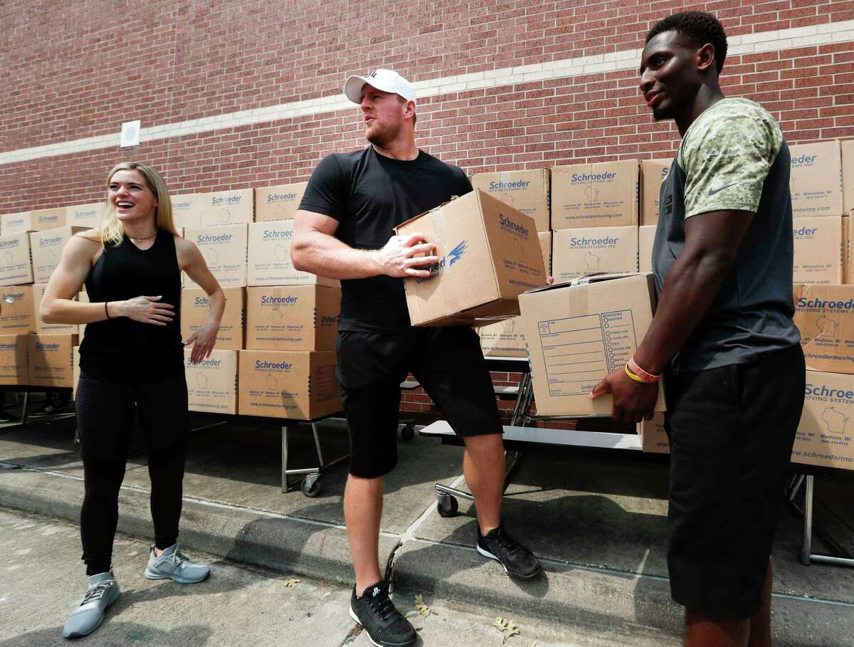 Houston Texans defensive end J.J. Watt, left, and running back Alfed Blue pick up boxes of relief supplies to distribute to people impacted by Hurricane Harvey on Sunday, Sept. 3, 2017, in Houston. J.J. Watt's Hurricane Harvey Relief Fund, which raised more than $17 million to date to help those affected by the storm.