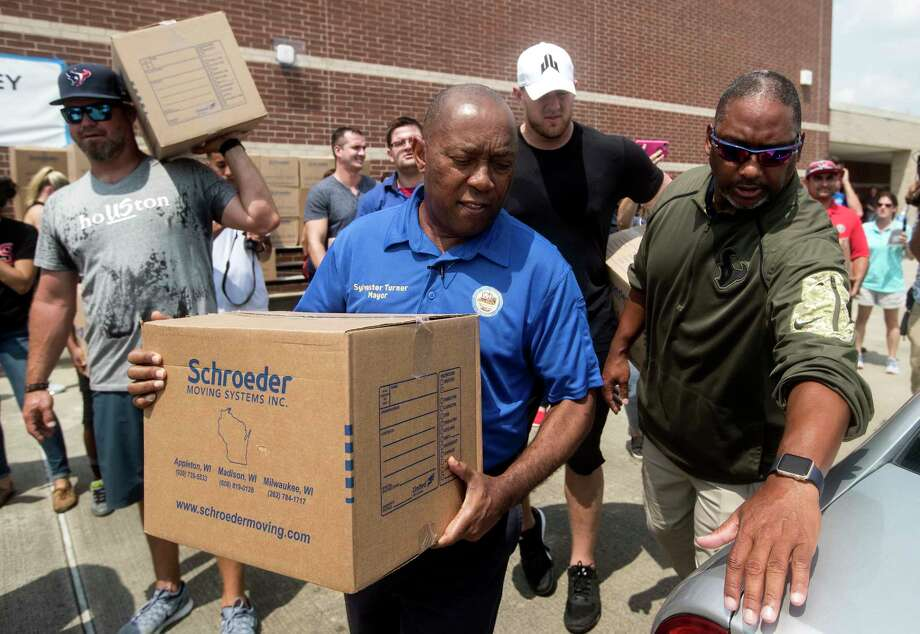 Houston Mayor Sylvester Turner, with Houston Texans Shane Lechler, left, and J.J. Watt distribute relief supplies to people impacted by Hurricane Harvey on Sunday, Sept. 3, 2017, in Houston. Watt's Hurricane Harvey Relief Fund has raised more than $18 million to date to help those affected by the storm. Photo: Brett Coomer, Houston Chronicle / © 2017 Houston Chronicle