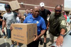 Houston Mayor Sylvester Turner, with Houston Texans Shane Lechler, left, and J.J. Watt distribute relief supplies to people impacted by Hurricane Harvey on Sunday, Sept. 3, 2017, in Houston. Watt's Hurricane Harvey Relief Fund has raised more than $18 million to date to help those affected by the storm.