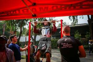 Julian Galves (center), dressed as a Royal Scottish guard does a pull up at the152nd Highland Gathering and Games in Pleasanton, Calif., on Sunday, Sept. 3, 2017.