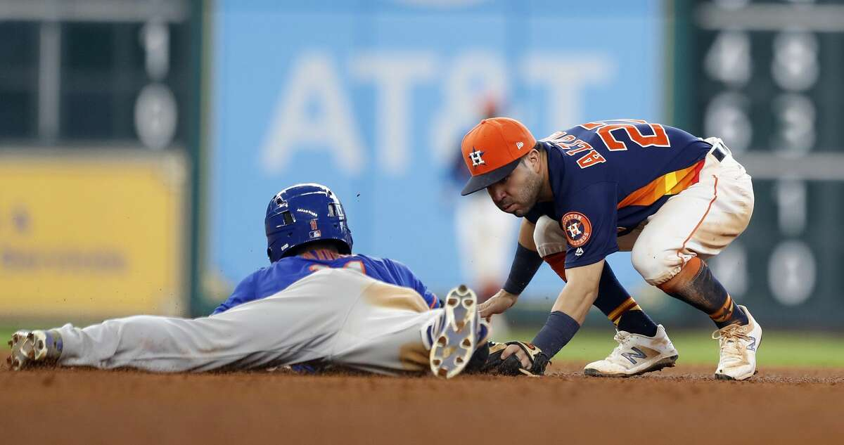Houston Astros second baseman Jose Altuve (27) tries to apply a tag on New York Mets Norichika Aoki (11) who doubled during the eighth inning of an MLB baseball game at Minute Maid Park, Sunday, Sept. 3, 2017, in Houston. ( Karen Warren / Houston Chronicle )