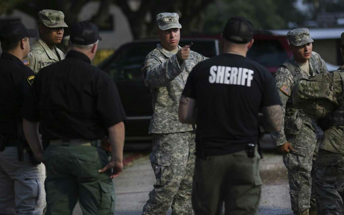 SGT 1ST Class Nicholas Loy, center, talks with Wharton County Sheriff Deputies as Members of the 49th Transportation Battalion and 1ST Medical Brigade prepare to give aid in Wharton, Tx on Friday, Sept. 1, 2017.