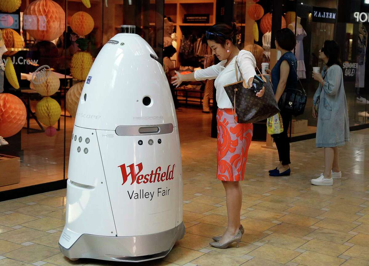 ADVANCE FOR RELEASE MONDAY, SEPT. 4, 2017, AT 12:01 A.M. EDT - In this Monday, June 26, 2017, photo, Sophie Li, of Cupertino, Calif., offers to dance with a K5 robot made by Knightscope, Inc., at Westfield Valley Fair shopping center in San Jose, Calif. In the technology hotbed that stretches from San Francisco to San Jose, people can eat a pizza made largely by a robot, have hotel toiletries delivered by a robot, drink a frothy cappuccino made by a robot and shop at a mall with robot security. Now, one prominent San Francisco official is calling for a tax on companies that automate jobs once held by people. (AP Photo/Ben Margot) ORG XMIT: NYBZ601