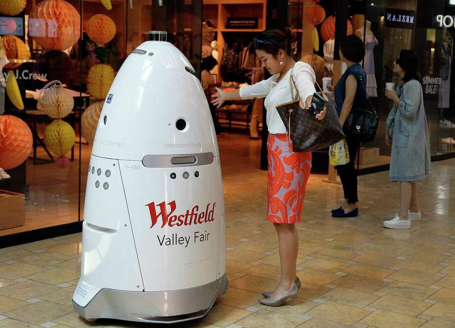 ADVANCE FOR RELEASE MONDAY, SEPT. 4, 2017, AT 12:01 A.M. EDT - In this Monday, June 26, 2017, photo, Sophie Li, of Cupertino, Calif., offers to dance with a K5 robot made by Knightscope, Inc., at Westfield Valley Fair shopping center in San Jose, Calif. In the technology hotbed that stretches from San Francisco to San Jose, people can eat a pizza made largely by a robot, have hotel toiletries delivered by a robot, drink a frothy cappuccino made by a robot and shop at a mall with robot security. Now, one prominent San Francisco official is calling for a tax on companies that automate jobs once held by people. (AP Photo/Ben Margot) ORG XMIT: NYBZ601 Photo: Ben Margot / Copyright 2017 The Associated Press. All rights reserved.