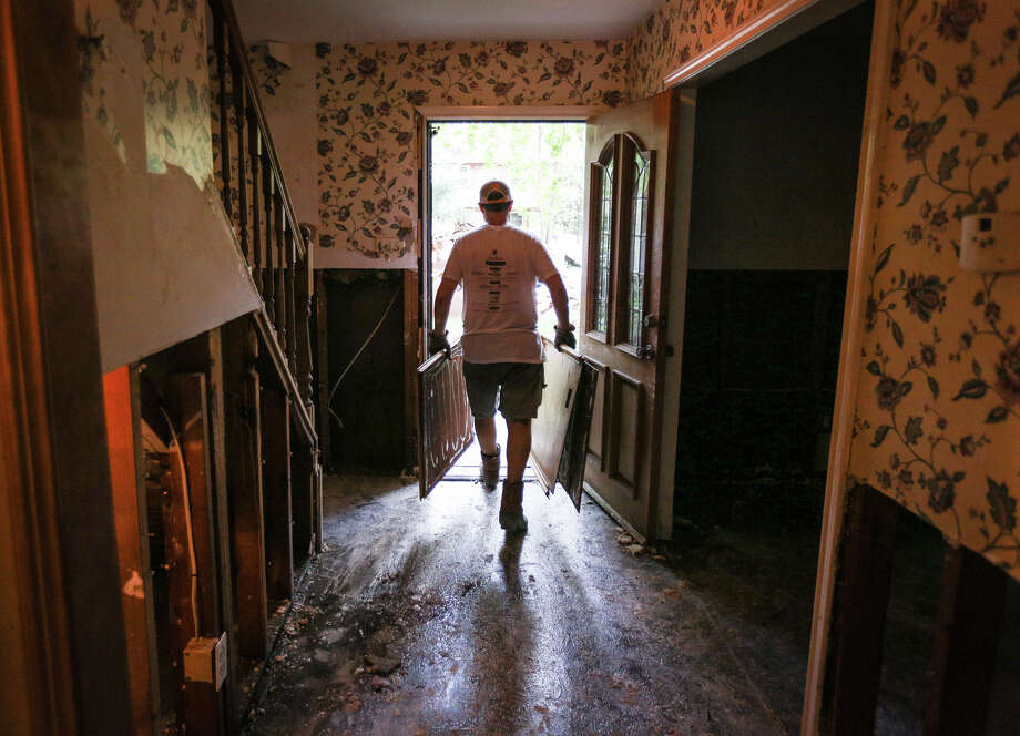 Ben Porter, a volunteer with Grace Crossing Church, carries out wood and drywall from the house of Woodloch Mayor Diane Lincoln on Saturday, Sept. 2, 2017, in Woodloch. Photo: Michael Minasi, Houston Chronicle / Internal