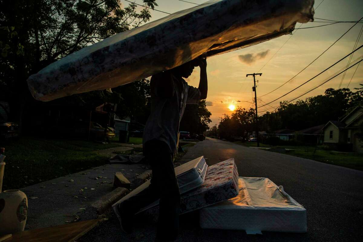 Phillip Jordan loads a mattress into his truck outside a flooded home on East 40th 1/2 Street in the Independence Heights neighborhood Sunday, Sept. 3, 2017 in Houston.