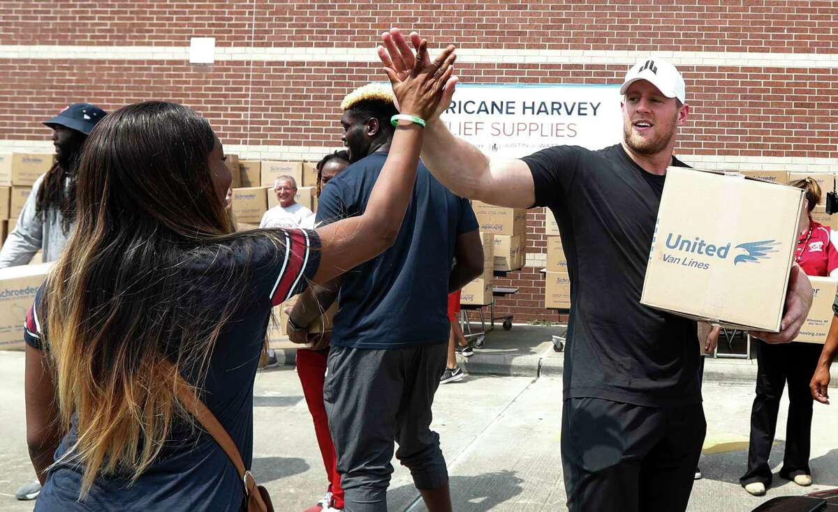 Anna Ucheomumu, left, high-fives Texans defensive end J.J. Watt after loading a car with relief supplies Sunday for people impacted by Hurricane Harvey. Several Texans helped Watt implement his relief efforts across the affected area.