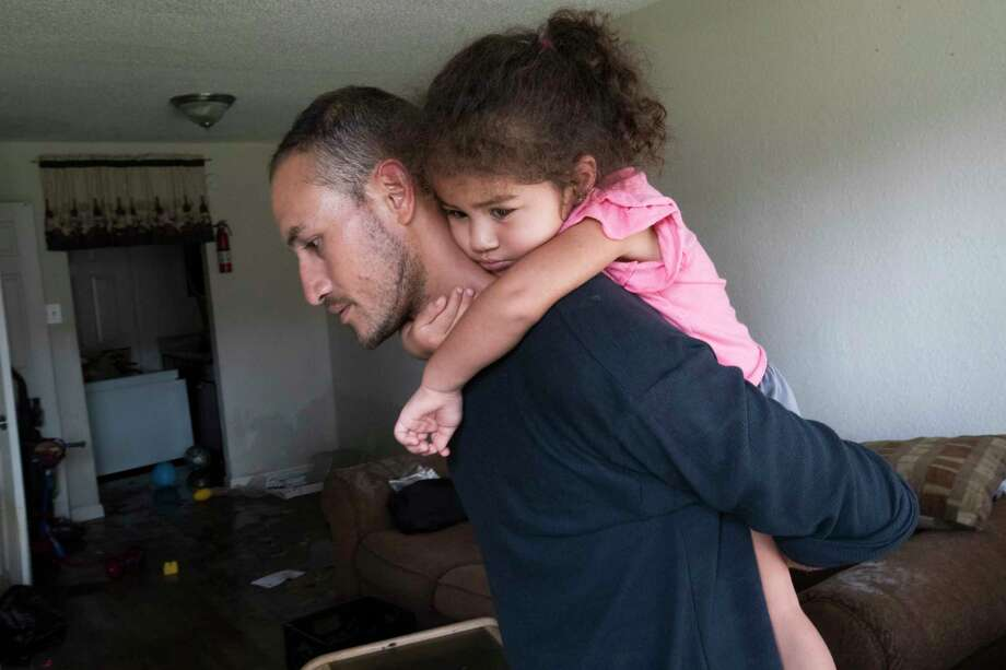 Byron Soto, 31, carries his daughter Kiara Soto, inside the apartment that got ruined by the flood caused by the Tropical Storm Harvey. The family is now working to relocate and to try to fix their two cars, Thursday, Aug. 31, 2017, in Houston. ( Marie D. De Jesus / Houston Chronicle ) Photo: Marie D. De Jesus, Staff / © 2017 Houston Chronicle