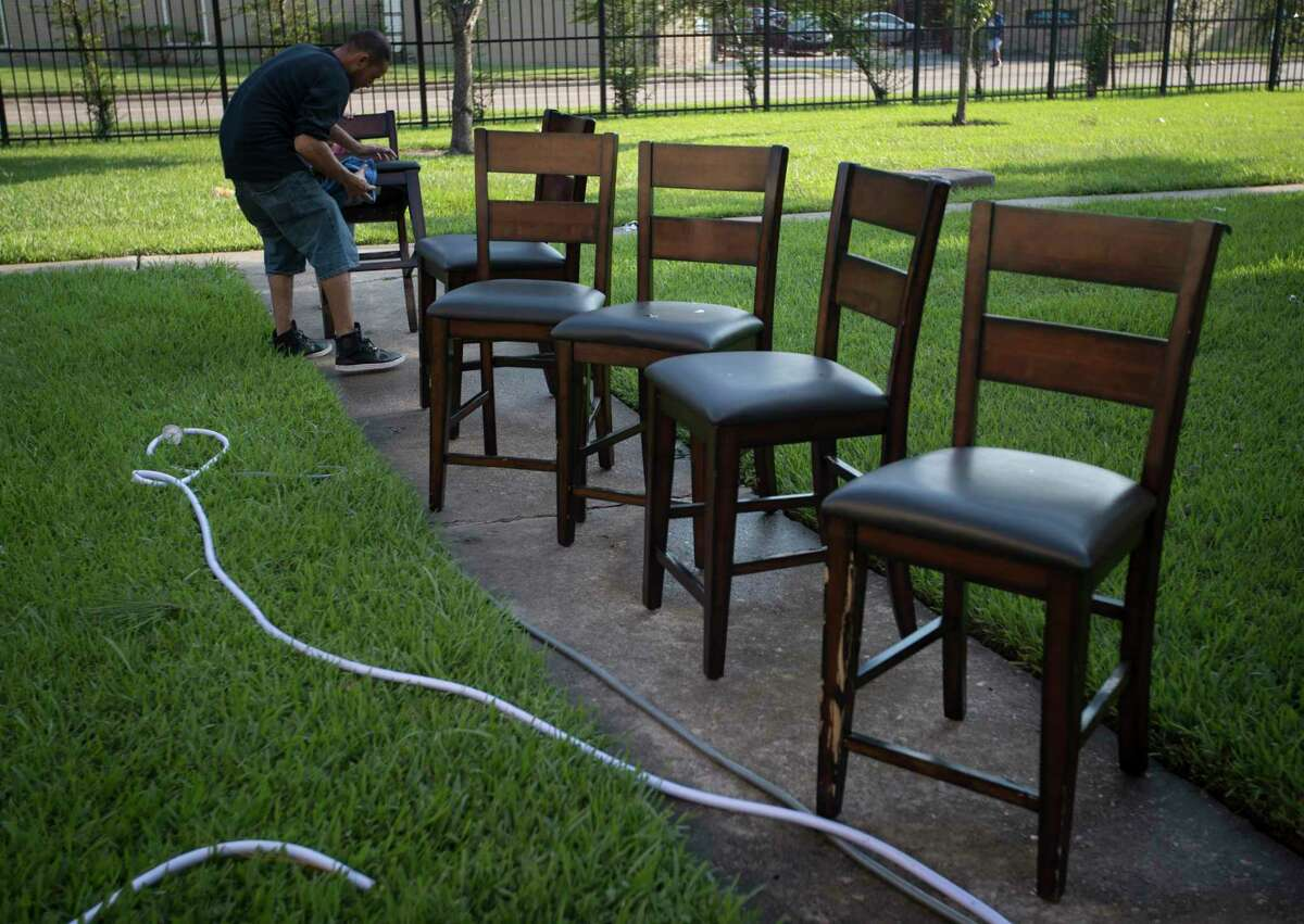 Byron Soto, 31, wipes off the dirt of flood waters from the dinning room chairs, Thursday, Aug. 31, 2017, in Houston. His family's apartment got flooded ruining their belongings as well as their two cars. ( Marie D. De Jesus / Houston Chronicle )