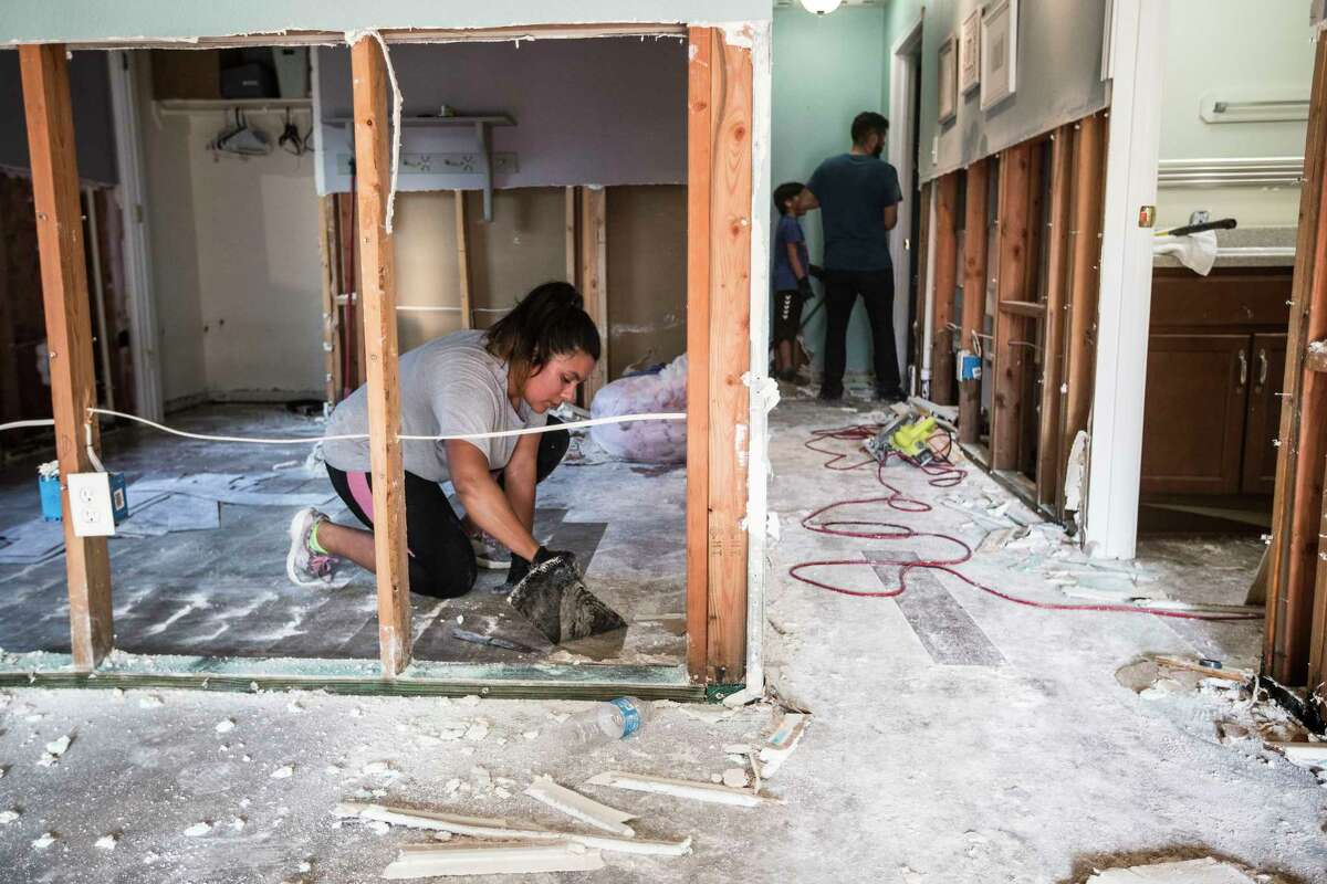 Mayra Rubio cleans out flooring in her mother's flood-damaged home in a neighborhood built by Habitat for Humanity on Saturday, Sept. 2, 2017, in Houston. ( Brett Coomer / Houston Chronicle )