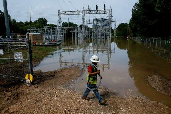 A CenterPoint Energy lineman navigates through a flooded substation where crews are working to bring power back online.