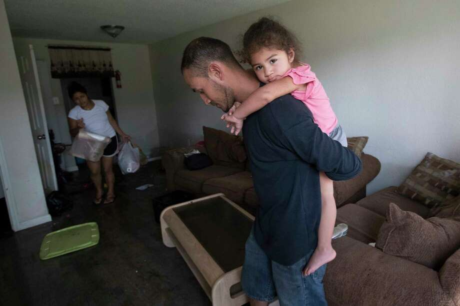 Byron Soto, 31, carries his daughter Kiara Soto, inside their Houston apartment, which got ruined by flood waters last week. Photo: Marie D. De Jesus, Houston Chronicle / © 2017 Houston Chronicle