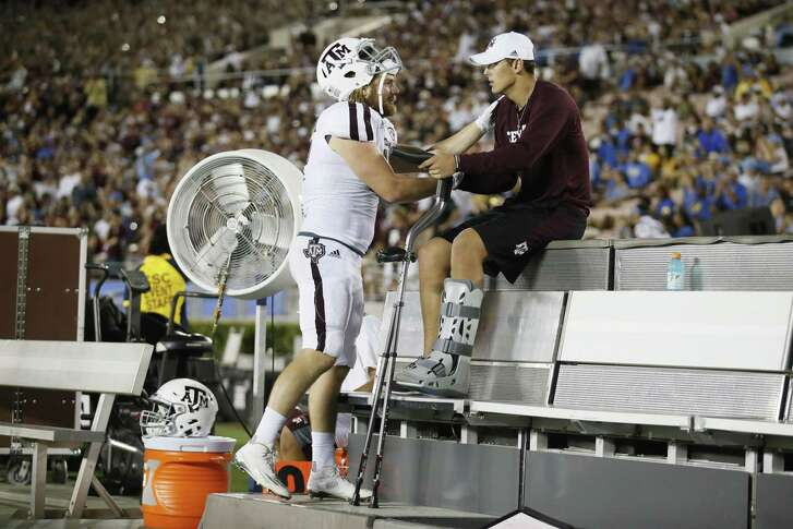 Texas A&M linebacker Cullen Gillaspia (left) checks on Texas A&M quarterback Nick Starkel, right, as he sits on the bench with an injury against UCLA on  Sept. 3, in Pasadena, Calif. Starkel is back quicker than many expected from a broken ankle. Coaches say he'll be available against Mississippi State on Saturday if needed.