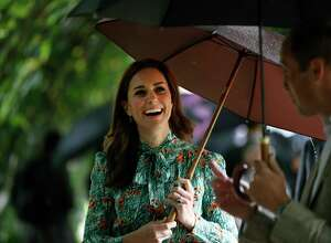 Britain's Prince William and his wife Kate, Duchess of Cambridge smile as they walk through the memorial garden in Kensington Palace, London, Wednesday, Aug. 30, 2017. Princes William and Harry are paying tribute to their mother, Princess Diana, on the eve of the 20th anniversary of her death by visiting the Sunken Garden to honor Diana's work with charities.