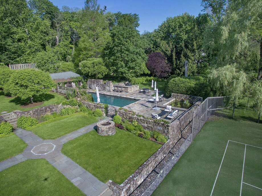 The lush two-acre property at 314 Brushy Ridge Road features flower and vegetable gardens, a tennis court and swimming pool.