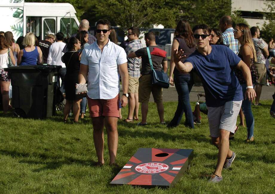 Joe Giarratana of Madison and Trevor Doherty of Fairfield play a game of Cornhole with friends during the Hey Stamford Food Fest at Mill River Park in Stamford on Aug. 25. Several thousand visitors to the festival enjoyed samplings of various local food truck vendors, a beer garden and live music of local area bands. Photo: Matthew Brown / Hearst Connecticut Media / Stamford Advocate