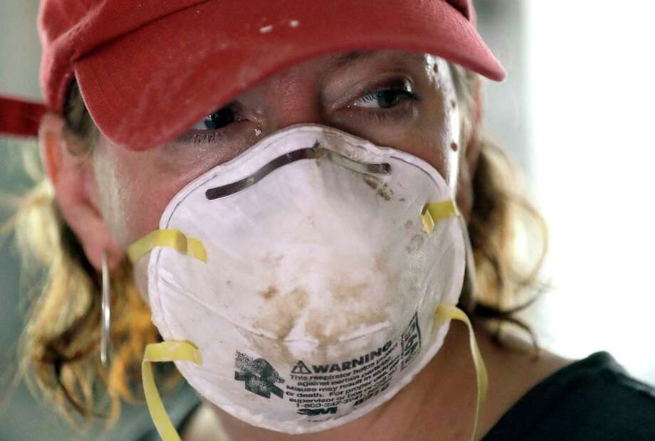 Volunteer Adrienne Adair wears a mask while helping clean up a home destroyed by floodwaters in the aftermath of Hurricane Harvey Sunday, Sept. 3, 2017, in Spring, Texas. (AP Photo/David J. Phillip) Photo: David J. Phillip, Associated Press / Copyright 2017 The Associated Press. All rights reserved.
