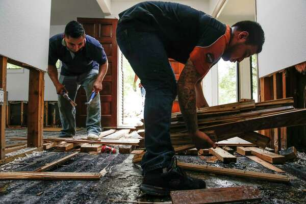 LC General Contractors employees Raul Gutierrez, left, and Misael Castillo, right, help to clear out a flooded home in Bellaire. The local contractors, accredited by the BBB, were remodeling the home when Harvey hit and transitioned from fixing the home to gutting it.