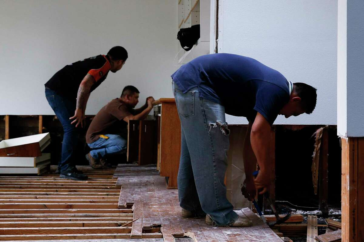 Workers with LC General Contractors help to rip up floorboards and clear out a flooded home Sunday, Sept. 3, 2017 in Belaire. The contractors were remodeling the home when Harvey hit and transitioned from fixing the home to gutting it. ( Michael Ciaglo / Houston Chronicle)