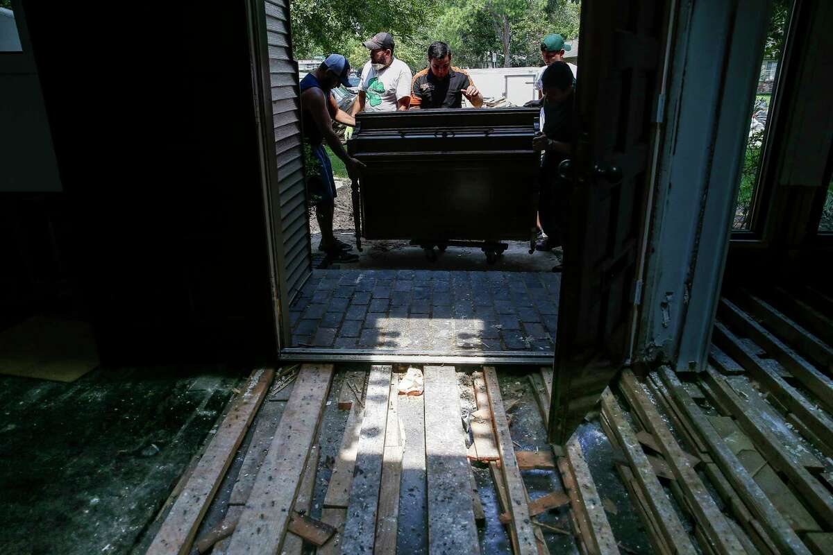 Workers with LC General Contractors move a piano out of a flooded home Sunday, Sept. 3, 2017 in Bellaire. The contractors were remodeling the home when Harvey hit and transitioned from fixing the home to gutting it. ( Michael Ciaglo / Houston Chronicle)