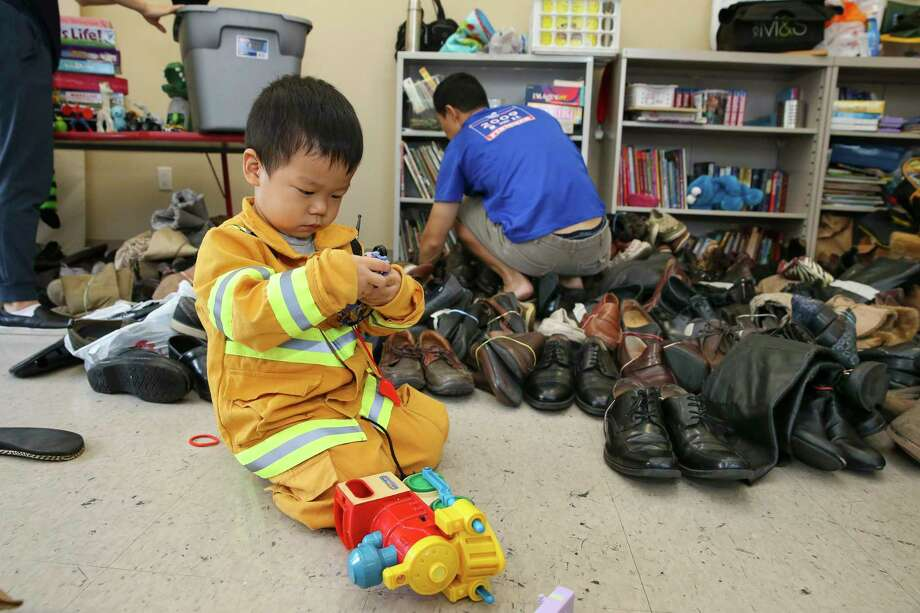 Gideon Kim, 2, with his dad, Nathan Kim, volunteer at The Forge for Families in Third Ward. Photo: Yi-Chin Lee, Staff / © 2017  Houston Chronicle
