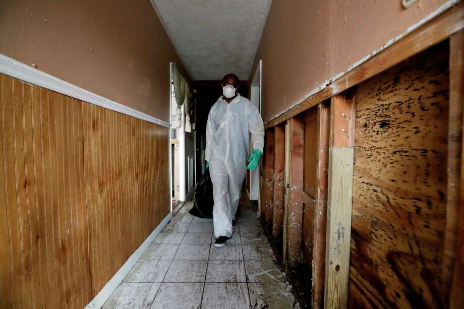 Donald Charles wears a protective suit and mask as he cleans out a flood-damaged home. Photo: Gregory Bull, STF / Copyright 2017 The Associated Press. All rights reserved.