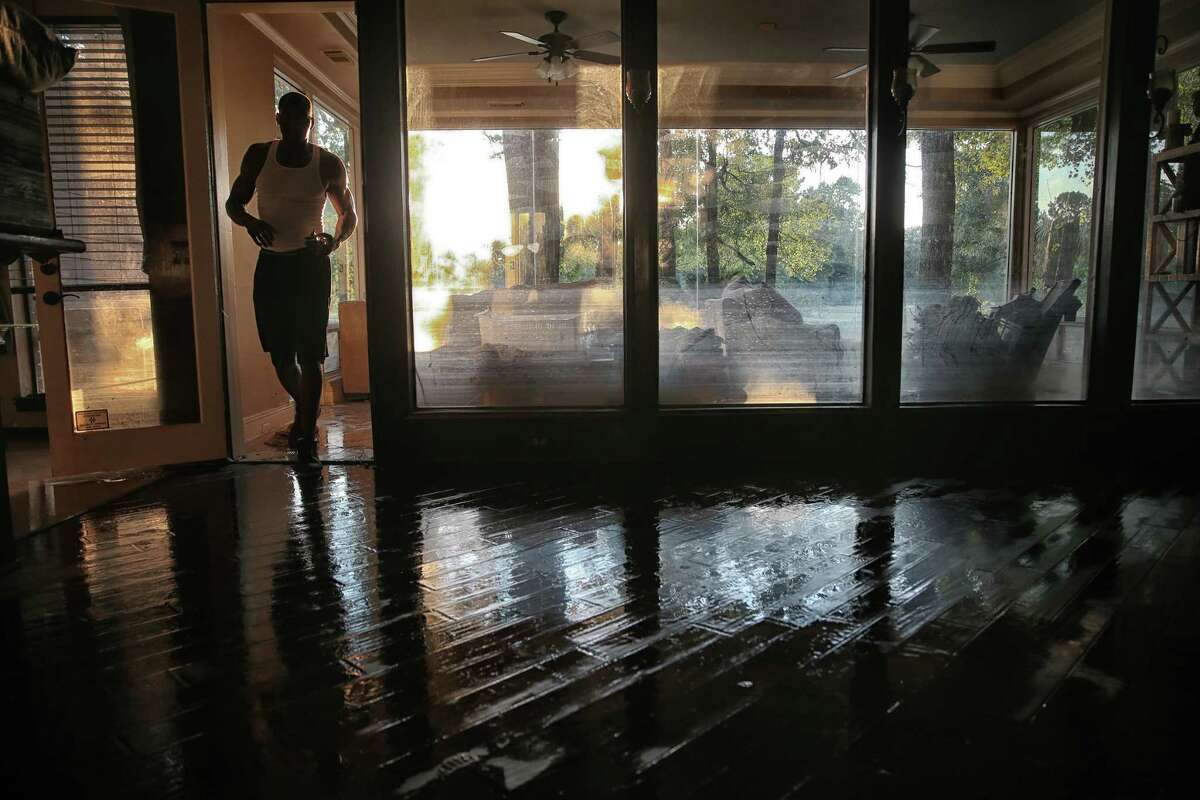 Bordered by a window showing the peak of the water level and stripped of it's flood damaged furniture, Charles Lewis walks into his living room while locking up his home in Kingwood, Texas, North of Houston, on August 31, 2017. (Robert Gauthier/Los Angeles Times/TNS)