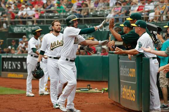 A's Jed Lowrie, 8 and Matt Joyce,23 score on a first inning double by Khris Davis, 2 that scored 3 runs, as the Oakland Athletics take on the Los Angeles Angels at the Oakland Coliseum in Oakland, Ca. on Mon. September 4, 2017.