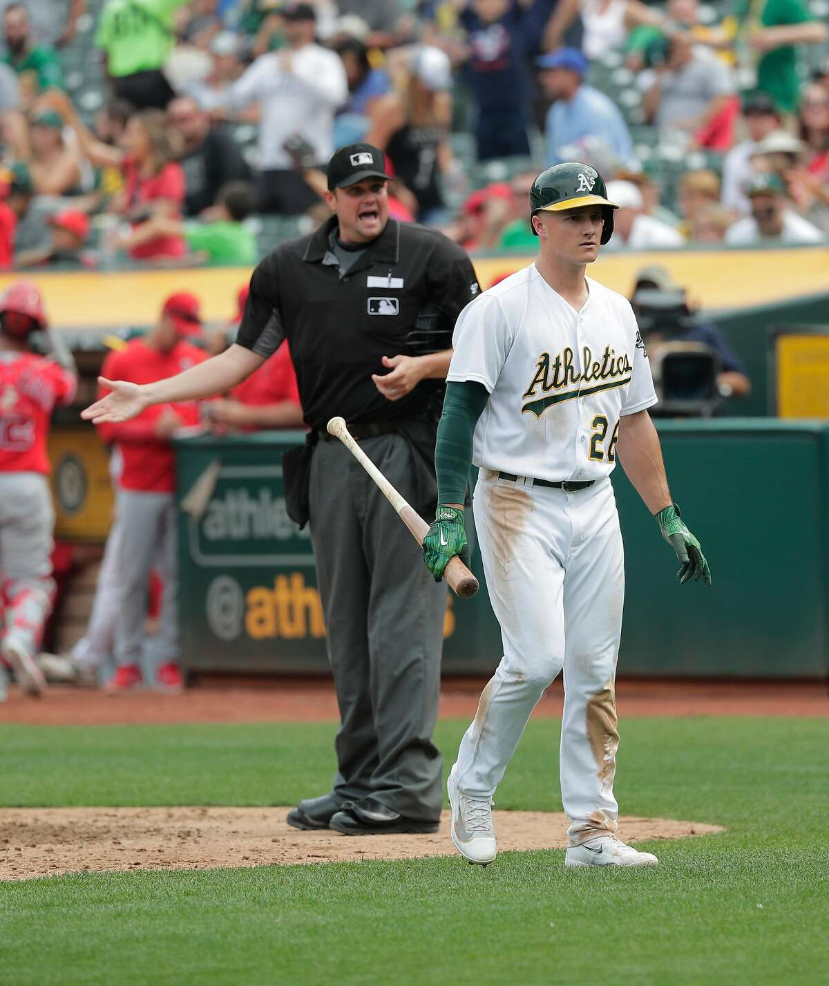 A's Matt Chapman, 26 walks back to the dugout after being called out looking to end the sixth inning as home plate umpire Jordan Baker barks back at Chapman, as the Oakland Athletics take on the Los Angeles Angels at the Oakland Coliseum in Oakland, Ca. on Mon. September 4, 2017.