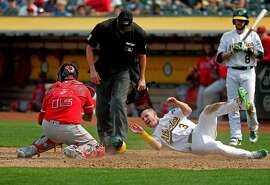 A's Boog Powell, 3 is out at home trying to steal from third base in the sixth inning, tagged out by the Angels' catcher Martin Maldonado, 12, as the Oakland Athletics take on the Los Angeles Angels at the Oakland Coliseum in Oakland, Ca. on Mon. September 4, 2017.