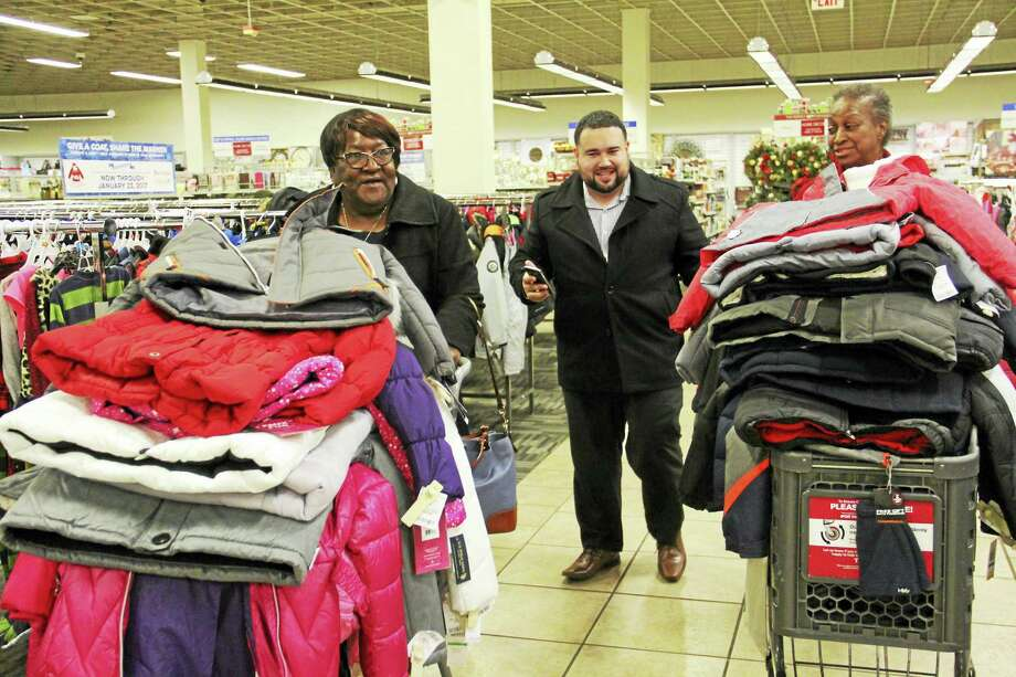 From left: Sarah McIver, New Haven Alder Dave Reyes and Thommye Shaw of the Hill South Management Team push carts with children's jackets at the Burlington Coat Factory in Orange. Photo: File Photo