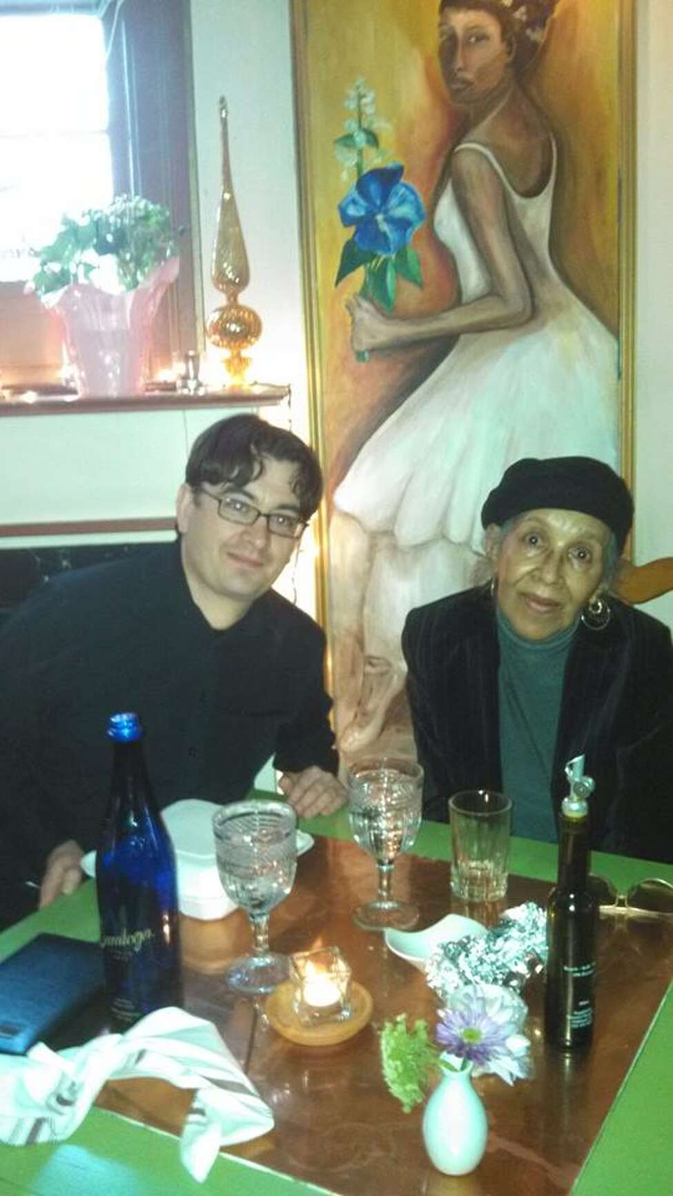 A 2014 photo of Aaron Pedinotti, left, in the Saratoga Springs restaurant his parents bought and named after Mia Mouzon, right, who grew up there. The portrait of Mouzon on the wall was painted by Aaron's sister, Rebecca Pedinotti. (Photo provided by Aaron Pedinotti)